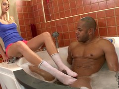 Clothed long legged kirmess Erica Fontes and naked coloured guy have some fun in the bathroom. He takes a bath as she gives footjob near her white socks on.